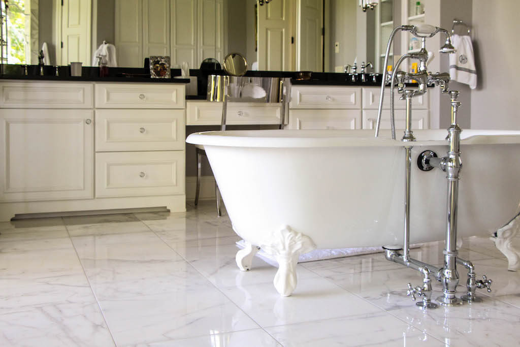 white clawfoot tub with vanity area in the background