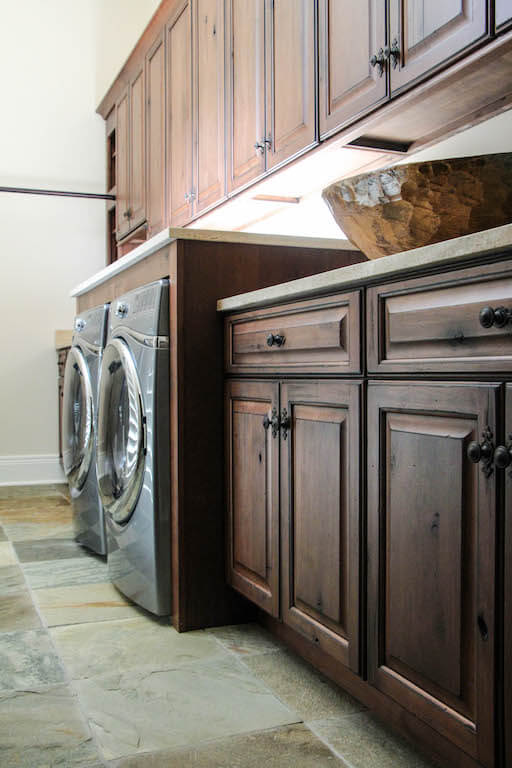 counters, cabinets, and storage built in a custom-designed laundry room