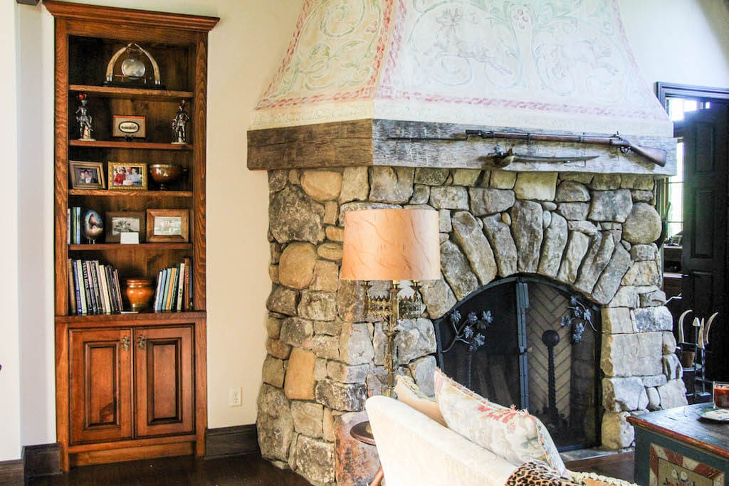 narrow built-in bookcase next to grand fireplace