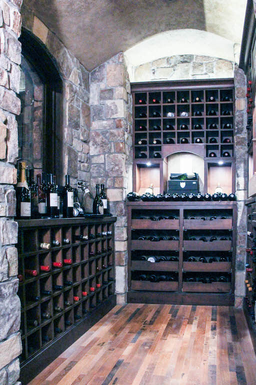 wine cellar with rock walls, dark wood storage areas