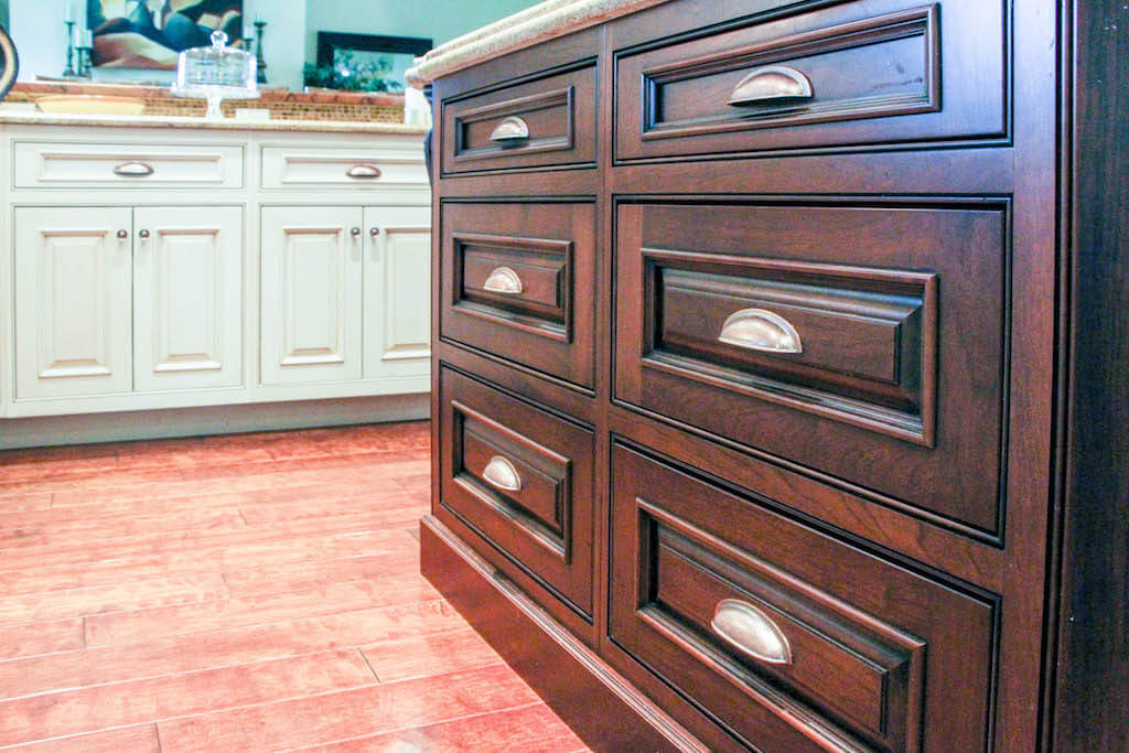 dark brown cabinet drawers on island with white kitchen cabinetry in background