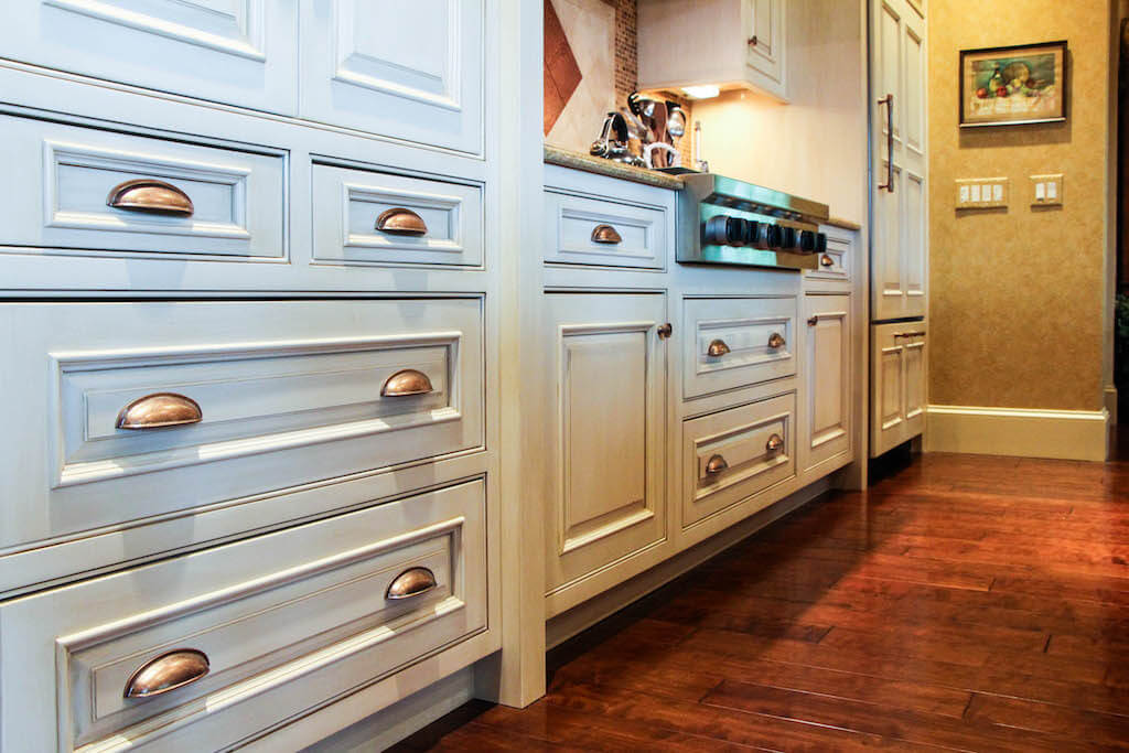 white kitchen cabinetry with copper-colored hardware
