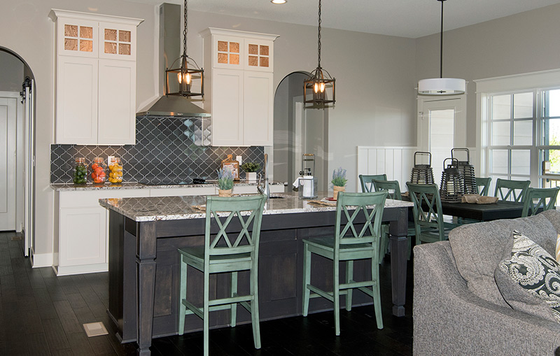 open concept kitchen, living, dining area, white cabinets, dark island and green chairs